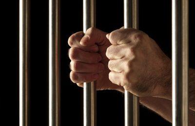Person Inside The Prison Bars