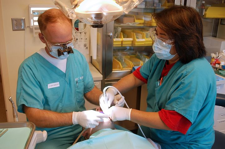 Two dentists performing wisdom teeth removal procedure in Windsor on a client