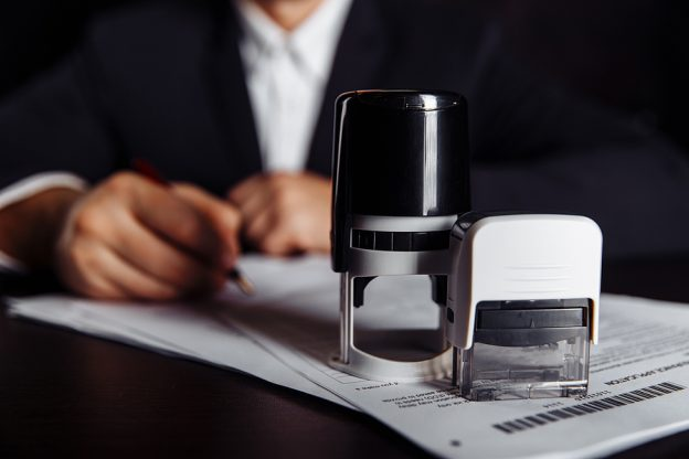 Businessman using ink stamps on documents